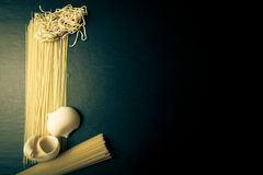 Different kinds of pasta on a black background. Space for text. Royalty Free Stock Image