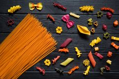 Different kinds of pasta on black background. Yellow conchiglie, color farfalline, orange tomato spaghetti, ping, green and. Purple stock photos