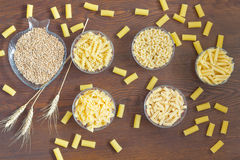 Different kinds of pasta in glass plates. Grains of wheat. And wheat spikelets on the table. Top View stock photos