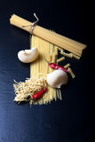 Different kinds of pasta and  red chili pepper on a black backgr Stock Image
