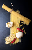 Different kinds of pasta and  red chili pepper on a black backgr Stock Photos