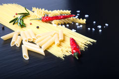 Different kinds of pasta, red chili pepper, rosemary, sea salt a Royalty Free Stock Photos