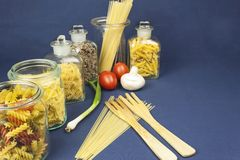 Different kinds of pasta on the table, together with vegetables Royalty Free Stock Photos