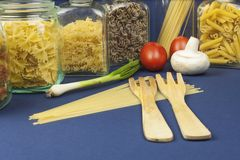 Different kinds of pasta on the table, together with vegetables Stock Image
