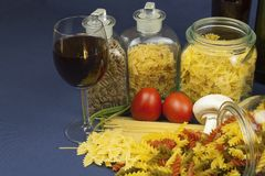 Different kinds of pasta on the table, together with vegetables Stock Photo