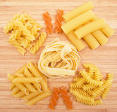 Different kinds of pasta on the wooden background Royalty Free Stock Photos