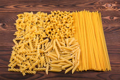 Different kinds of pasta on a wooden background. Farfalle, fettuccine, noodles, fusilli and penne rigate. Tasty Italian cuisine. Royalty Free Stock Photo