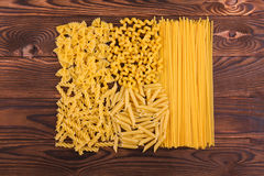 Different kinds of pasta on a wooden background. Farfalle, fettuccine, noodles, fusilli and penne rigate. Tasty Italian cuisine. Stock Images