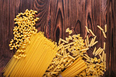 Different kinds of pasta on a wooden background. Farfalle, fettuccine, noodles, fusilli and penne rigate. Tasty Italian Stock Images
