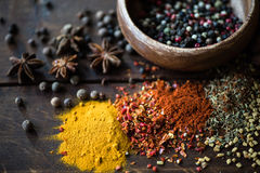 Different kinds of pepper in bowl and spices with herbs scattered. On wooden tabletop royalty free stock photo