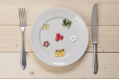 Different kinds of pills on plate and fork with knife. Strict diet. Plate of medicines as replacement for a meal Stock Image