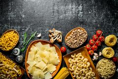 Different kinds of raw pasta with tomatoes and mushrooms. On black rustic background royalty free stock photography