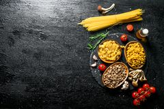 Different kinds of raw paste in bowls with tomatoes, garlic and mushrooms. On black rustic background stock photo