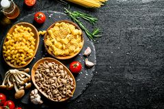 Different kinds of raw paste in bowls with tomatoes, garlic and mushrooms. On black rustic background royalty free stock images