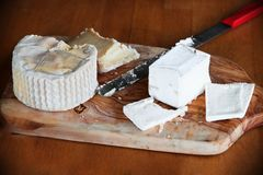 Various types of cheese on wooden board with knife. Royalty Free Stock Image