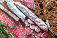 Different kinds of salami with dark-rye bread Stock Photos