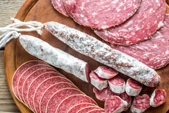 Different kinds of salami. On the wooden board Stock Images