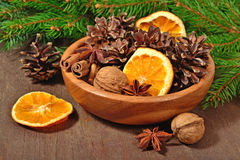 Different kinds of spices, nuts, dried oranges and cones in bowl Royalty Free Stock Photos