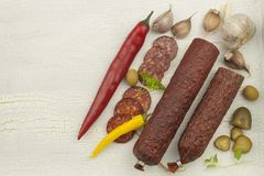 Different kinds of spicy salami on cracked shadowed background. Preparing home celebrations. Refreshments for a visit. Production of sausages stock images