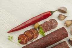 Different kinds of spicy salami on cracked shadowed background. Preparing home celebrations. Refreshments for a visit. Production of sausages royalty free stock images