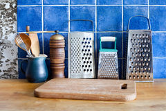 Different kinds stainless steel grater, green jug,  spoons, cutting board. Stock Images