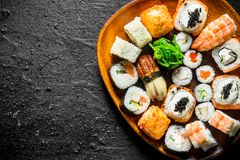 Different kinds of sushi rolls on the plate. On black rustic background royalty free stock images
