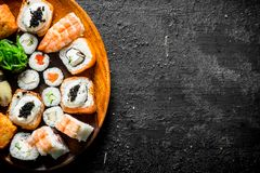 Different kinds of sushi rolls on the plate. On black rustic background royalty free stock photos