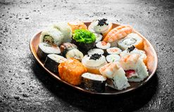 Different kinds of sushi rolls on the plate. On black rustic background stock image