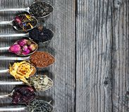 The different kinds of tea presented as a sample in the silver spoons, top view royalty free stock image