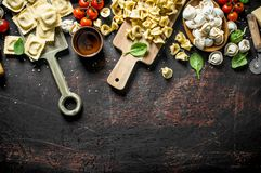 Different kinds of traditional Italian raw pasta. On dark rustic background royalty free stock photo