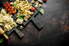 Different kinds of traditional Italian raw pasta. On dark rustic background stock image