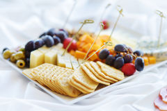 Different kinds of wine snacks: cheeses, crackers, fruits and olives on white table Royalty Free Stock Image