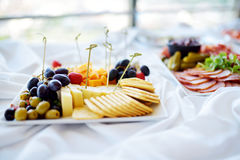 Different kinds of wine snacks: cheeses, crackers, fruits and olives on white table royalty free stock images