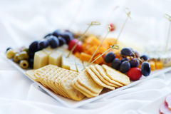 Different kinds of wine snacks: cheeses, crackers, fruits and olives on white table stock images