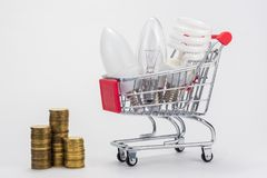 Different LED bulbs, energy-saving, incandescent are in the grocery cart, next to there are stacks of coins royalty free stock image