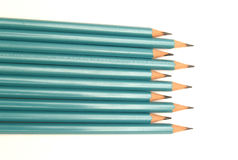 Different length pencils. Overhead view of row of different length teal colored pencils, white background Royalty Free Stock Photography