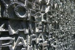 Different letters carved on a stone wall.  royalty free stock photography