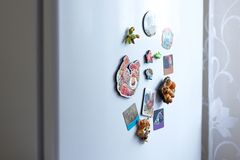 Different magnets on a white refrigerator in the kitchen. Closeu Royalty Free Stock Images