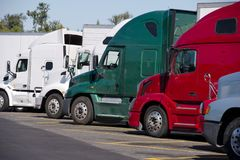 Different make and moders of big rigs semi trucks stand in row o stock photo