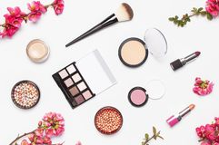 Different makeup cosmetic. Ball blush rouge face powder lipstick concealer bottle of perfume eyeshadow makeup brush spring pink. Flowers on light background top stock photography