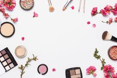 Different makeup cosmetic. Ball blush rouge face powder lipstick concealer bottle of perfume eyeshadow makeup brush spring pink. Flowers on light background top royalty free stock images