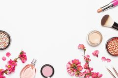Different makeup cosmetic. Ball blush rouge face powder lipstick concealer bottle of perfume eyeshadow makeup brush spring pink. Flowers on light background top stock image