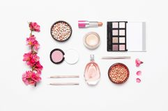 Different makeup cosmetic. Ball blush rouge face powder lipstick concealer bottle of perfume eyeshadow makeup brush spring pink. Flowers on light background top royalty free stock photography
