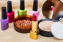 Lipstick, eye shadows, nail polish, powder. Different makeup products - lipstick, eye shadows, nail polish, powder stock images