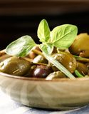 Different marinated olives and capers in a small ceramic bowl. royalty free stock photos