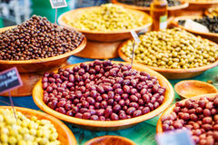 Different marinated olives on provencal street market in Provenc Stock Photo