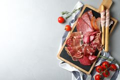 Different meat delicacies served on gray table, top view. Space for text royalty free stock image