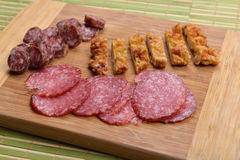 Different meat products (sausages, salami, breaded chicken breas. T) arranged on a wood trencher. Rustic food. Selective focus Stock Photo