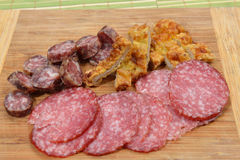 Different meat products (sausages, salami, breaded chicken breas. T) arranged on a wood trencher. Rustic food. Selective focus Royalty Free Stock Photography
