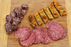Different meat products (sausages, salami, breaded chicken breas. T) arranged on a wood trencher. Rustic food. Selective focus Royalty Free Stock Image